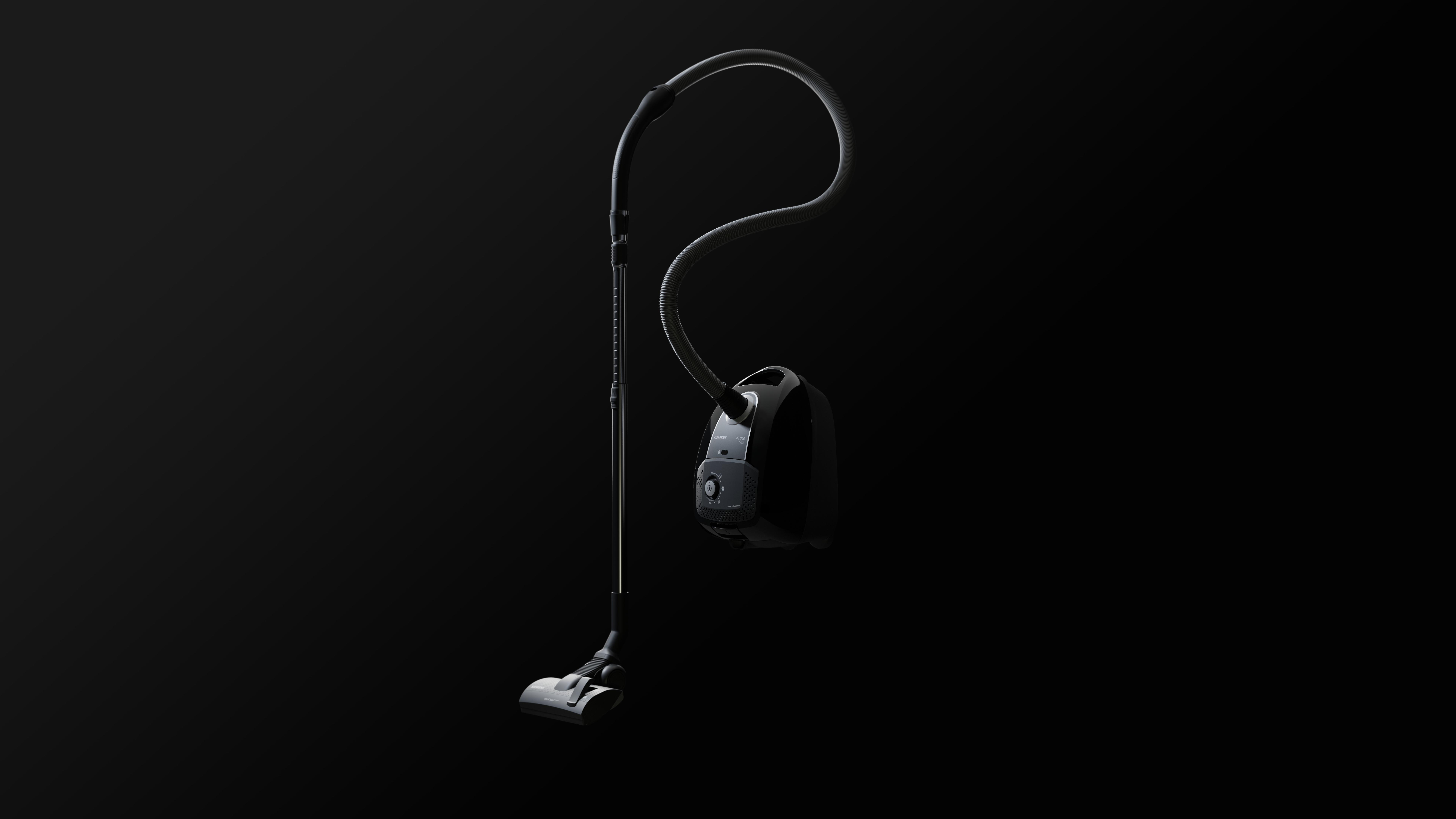 black vacuum cleaner standing on black background