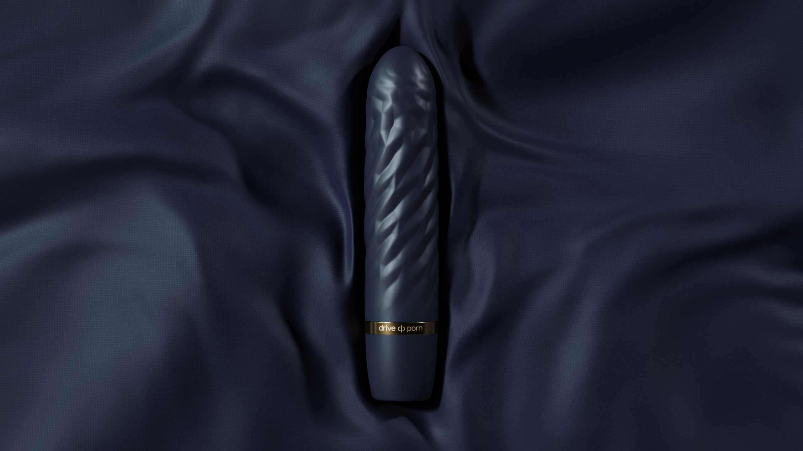 black structured adult toy with golden text lying on marine blue fabric