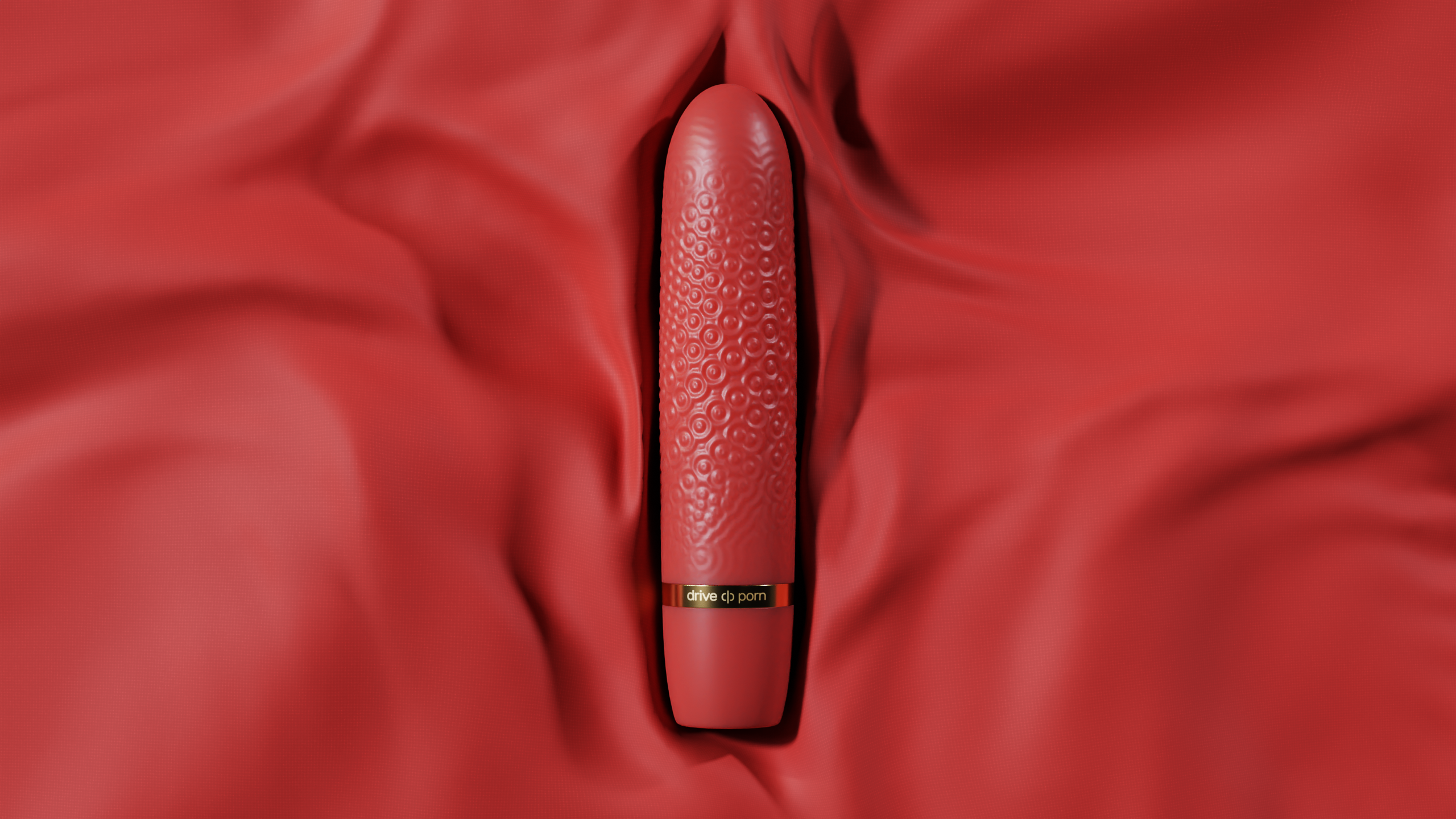 red structured adult toy with golden text lying on red fabric