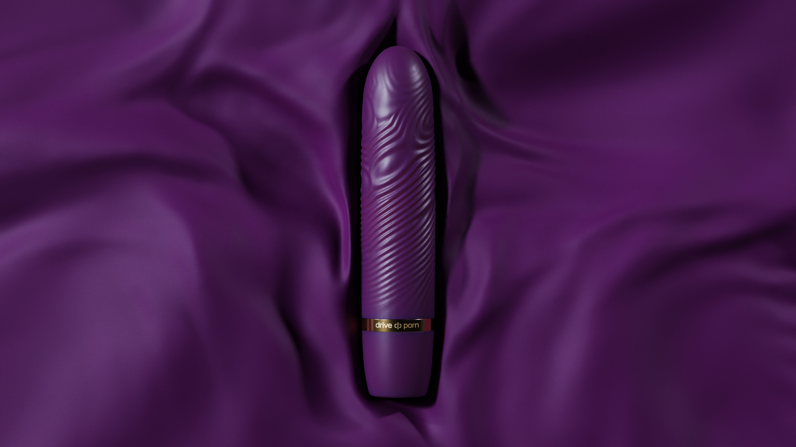 purple structured adult toy with golden text lying on purple fabric