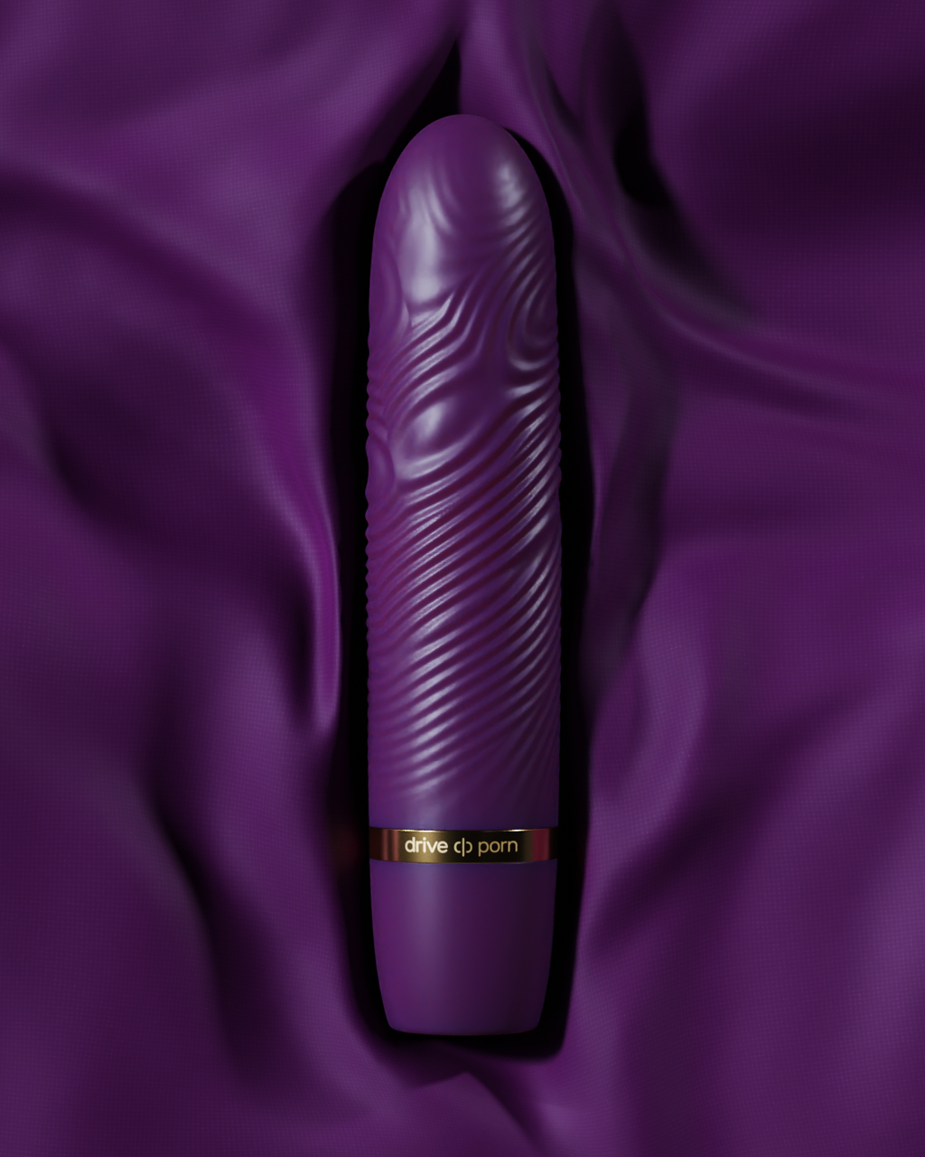 black adult toy with golden text lying on purple fabric