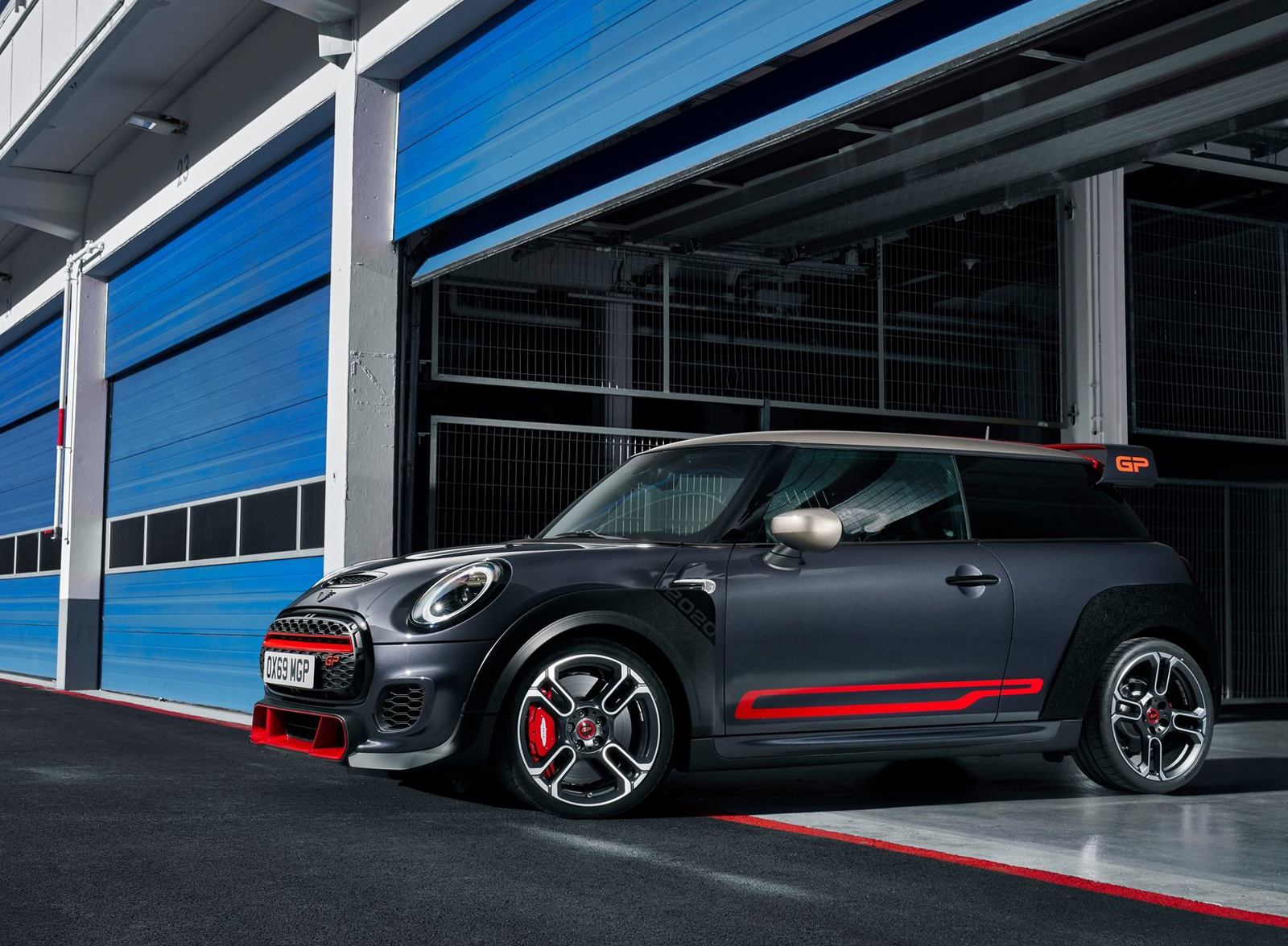 grey car MINI John Cooper with red highlights standing in blue garage