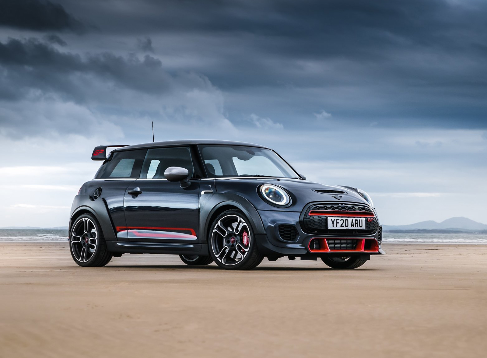 grey car MINI John Cooper with red highlights standing on cloudy beach