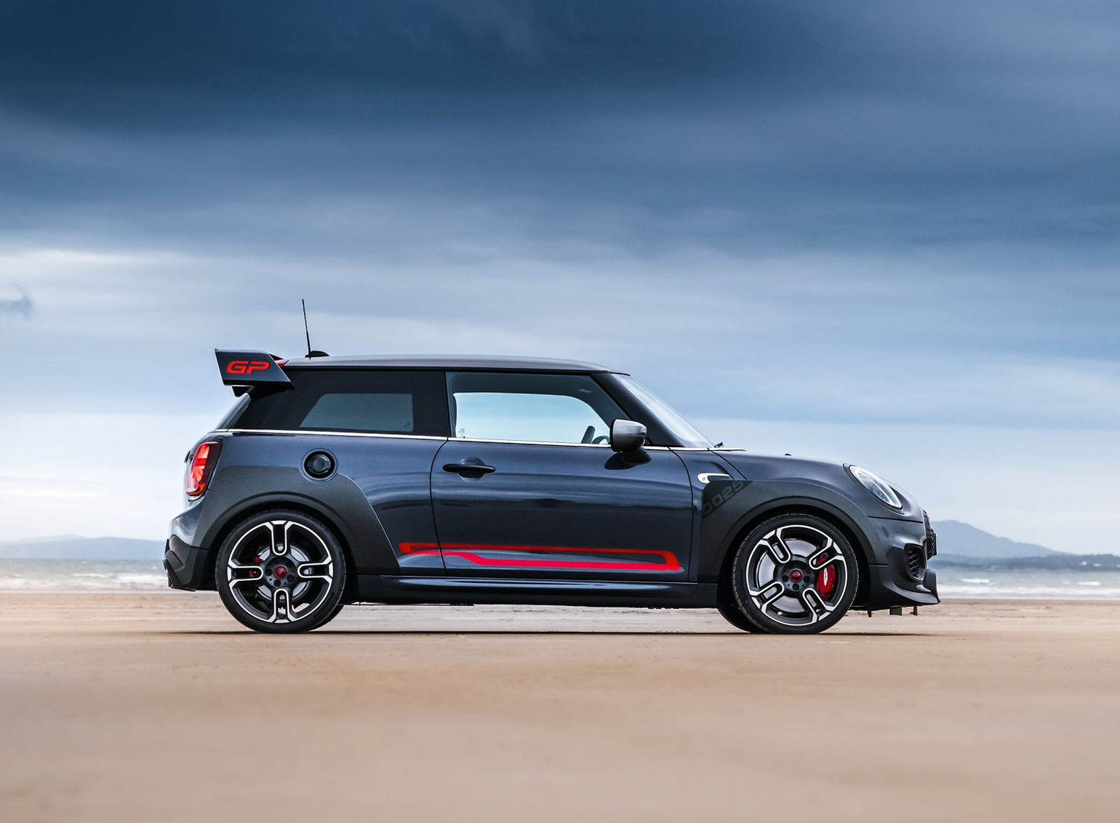 grey car MINI John Cooper with red highlights standing on cloudy beach side view