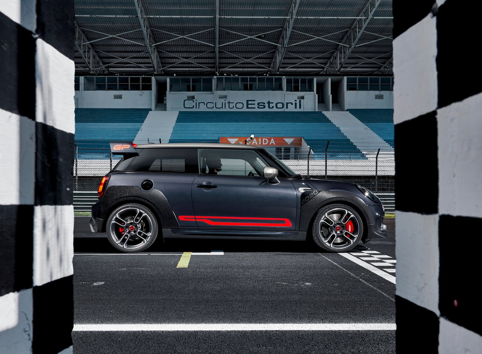 grey car MINI John Cooper with red highlights standing on start of race track